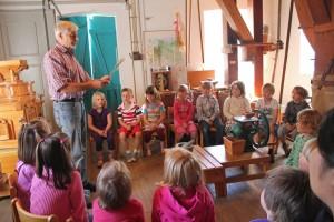Eine Kindergarten-Gruppe lernt hier verschiedene Getreide kennen, die dann in einem Mörser, einer kleinen Handmühle und einem elektrisch betriebenen Beutelgang zu Mehl verarbeitet werden. Foto: Rudolf Franke